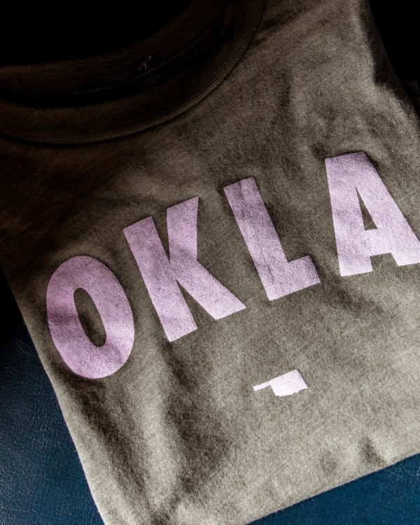 A mockup of a green kids onesie with OKLA printed on the front in light pink