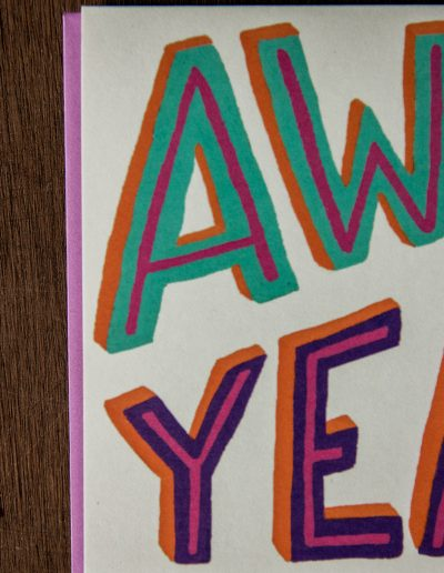 A white paper card that says 'Awww Yeah!' in purple and turquoise