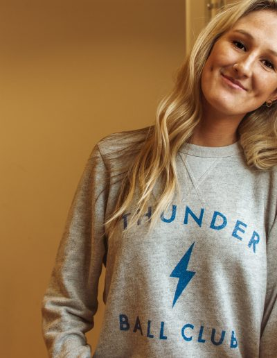 Woman wearing pullover sweatshirt that reads Thunder Ball Club