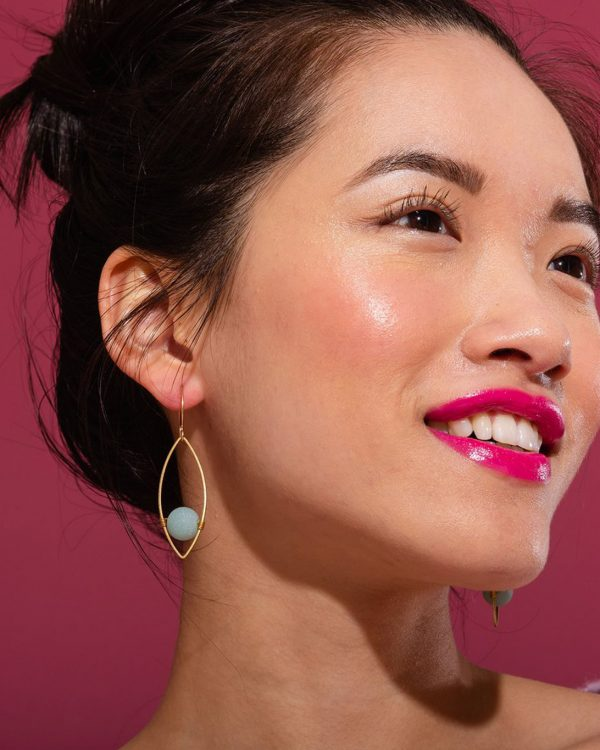 A woman wearing Gold earrings with rose quartz stones in the center