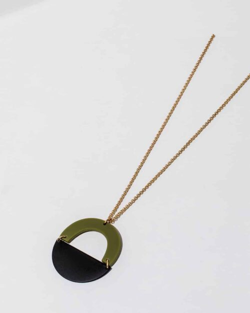 A brass necklace with green and black stones on the end