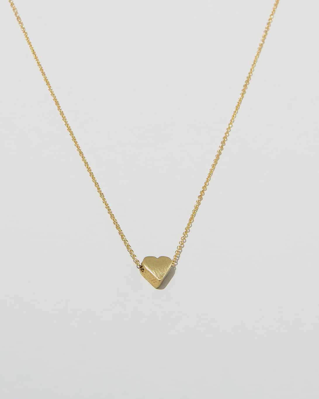 brass chain necklace with a heart on the end