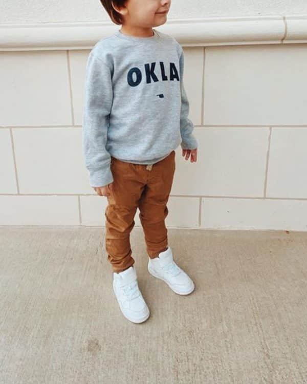 A photo of a kid wearing a grey pullover that says OKLA in navy blue ink