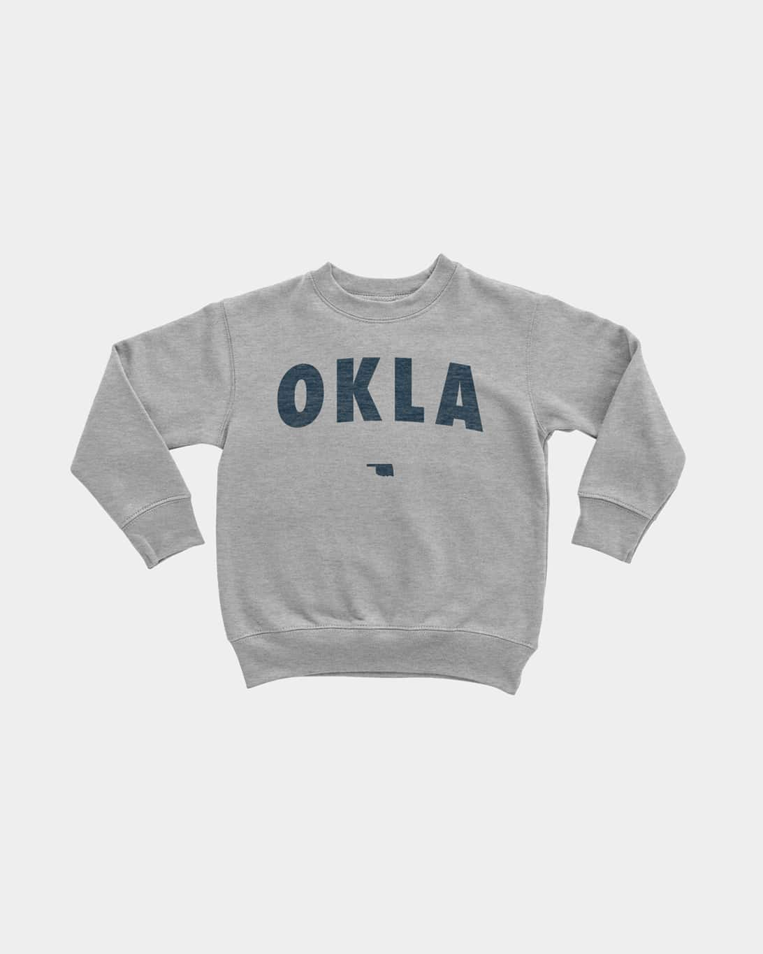 A mockup of a grey kid's pullover that says OKLA in navy blue ink