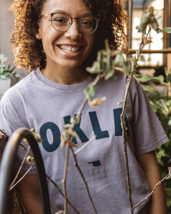 A women wearing an orchid colored tee with the word OKLA screen printed on the front in navy blue.