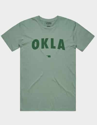 A green tee with OKLA screenprinted in sage green on the front