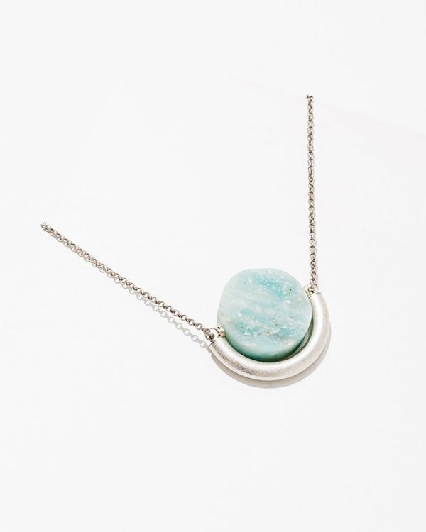 A turquoise and white stone on a brass chain