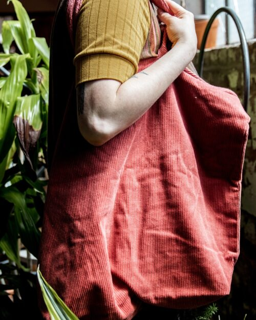 A detailed shot of a woman holding a red corduroy tote bag.