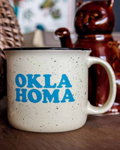 An almond campfire mug that says Oklahoma in light blue type
