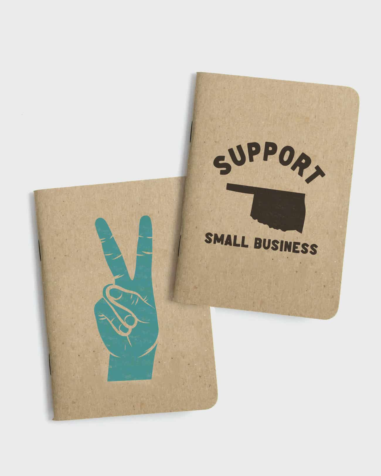 Set of 2 small kraft paper notebooks. Both with screen printed covers, the first with a support Oklahoma small business graphic, the second with peace sign hand graphic