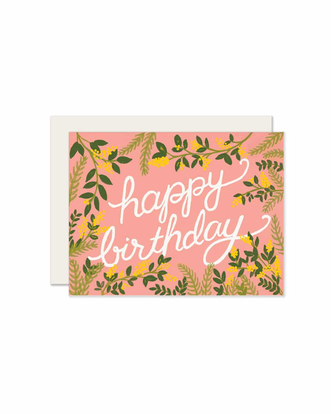 A pink, paper birthday card that says happy birthday surrounded by plants