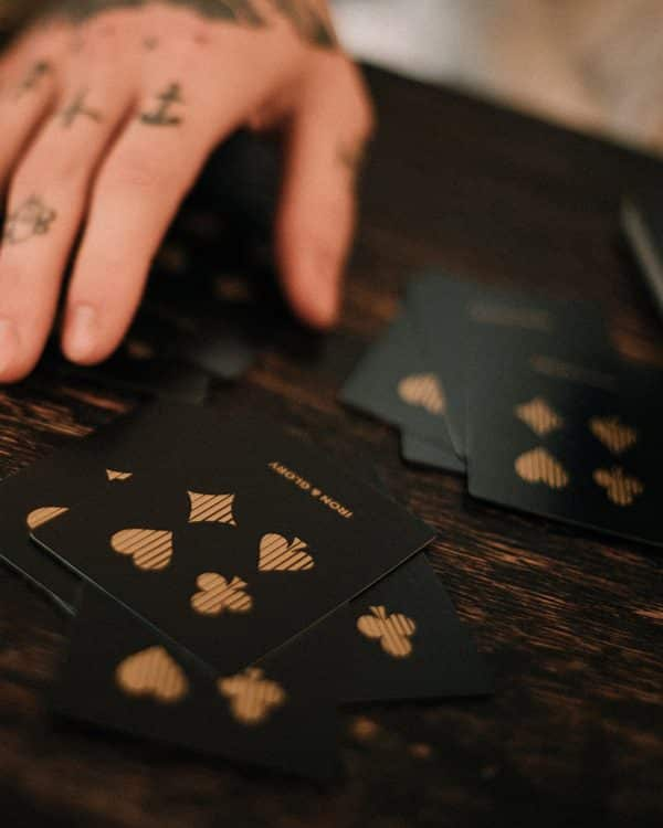 A hand dealing Up the Ante Playing card set