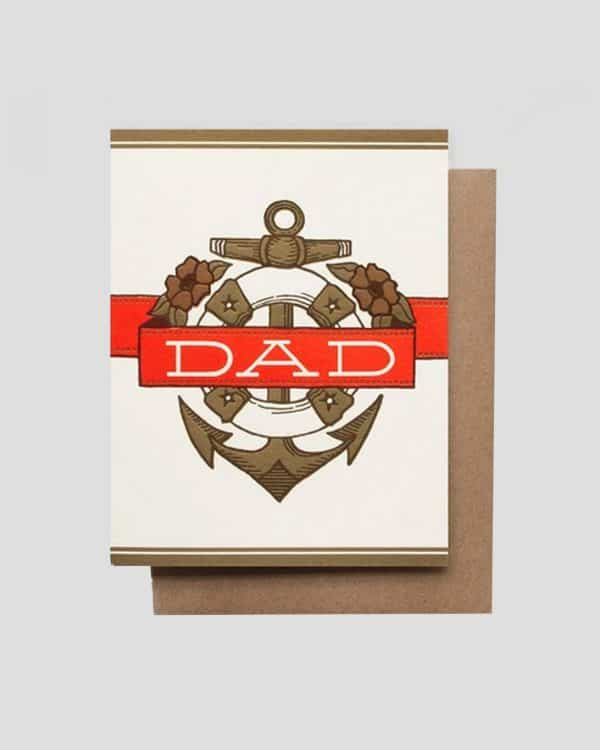 A white, red and brown paper card that says Dad on it in the middle of an anchor.