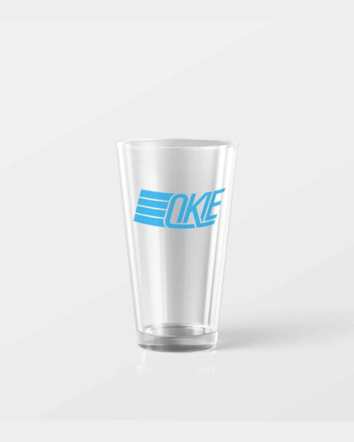 A 16 oz pint glass with the words Okie on it in light blue.