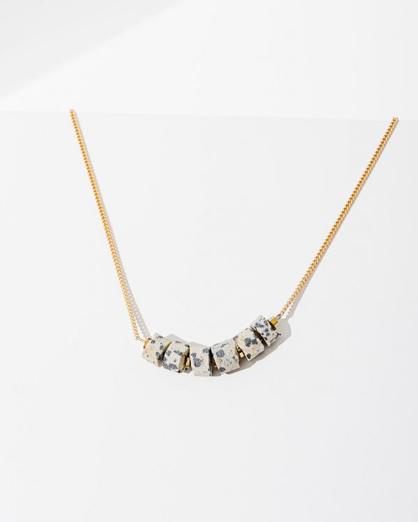 A brass necklace with rose quartz gemstones at the cusp of the chain.
