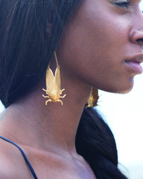 brass bee earrings hanging from a models ears