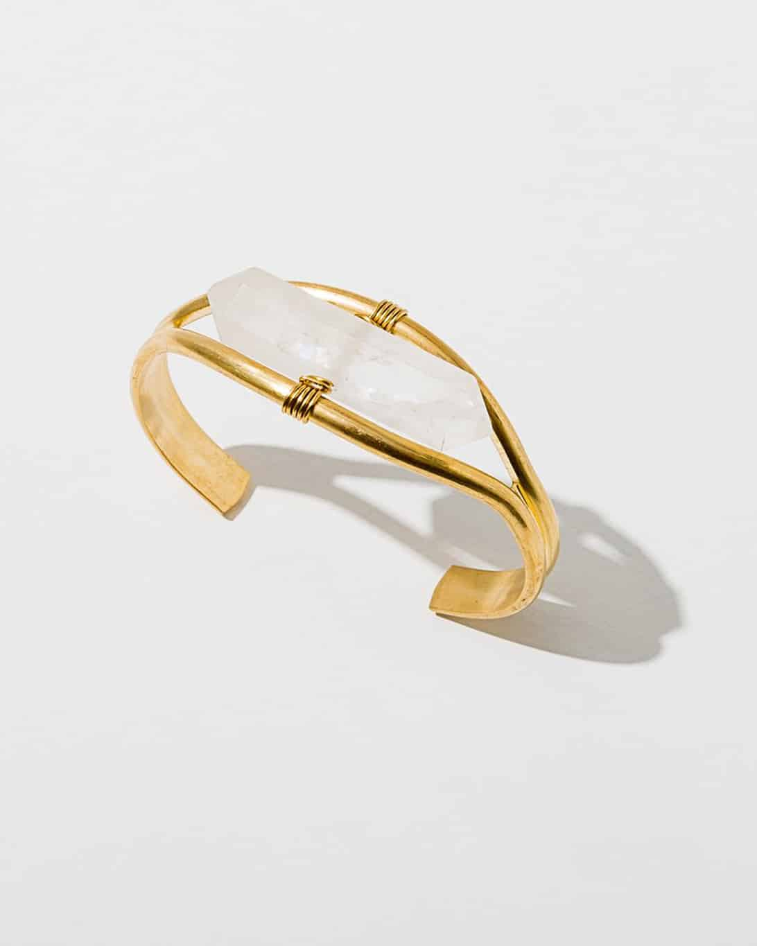 A brass banded cuff bracelet with a quartz gemstone in the center
