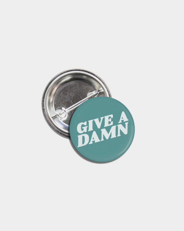A green tin pinback button that says Give A Damn in white.