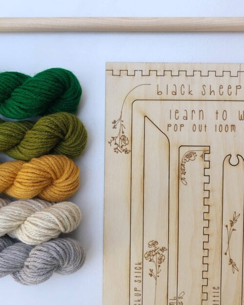 A photo of the DIY Woodland Tapestry Kit with greenm yellow, white and grey yarn