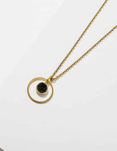 A photo of a gold kamilah necklace with a black stone at the center