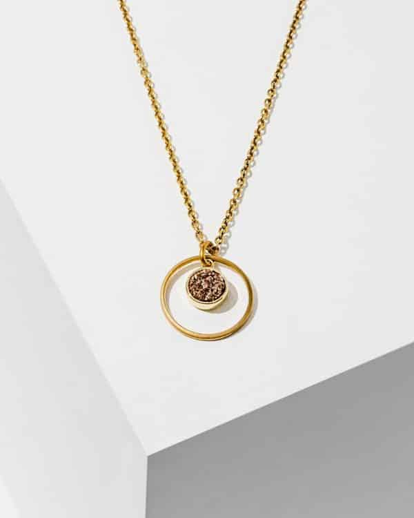 A gold necklace with a rose gold stone as the center piece