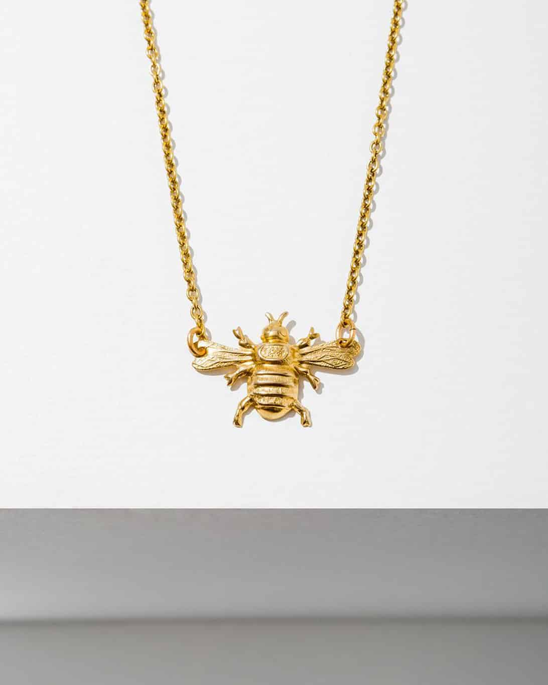 A brass necklace with a bee on the end