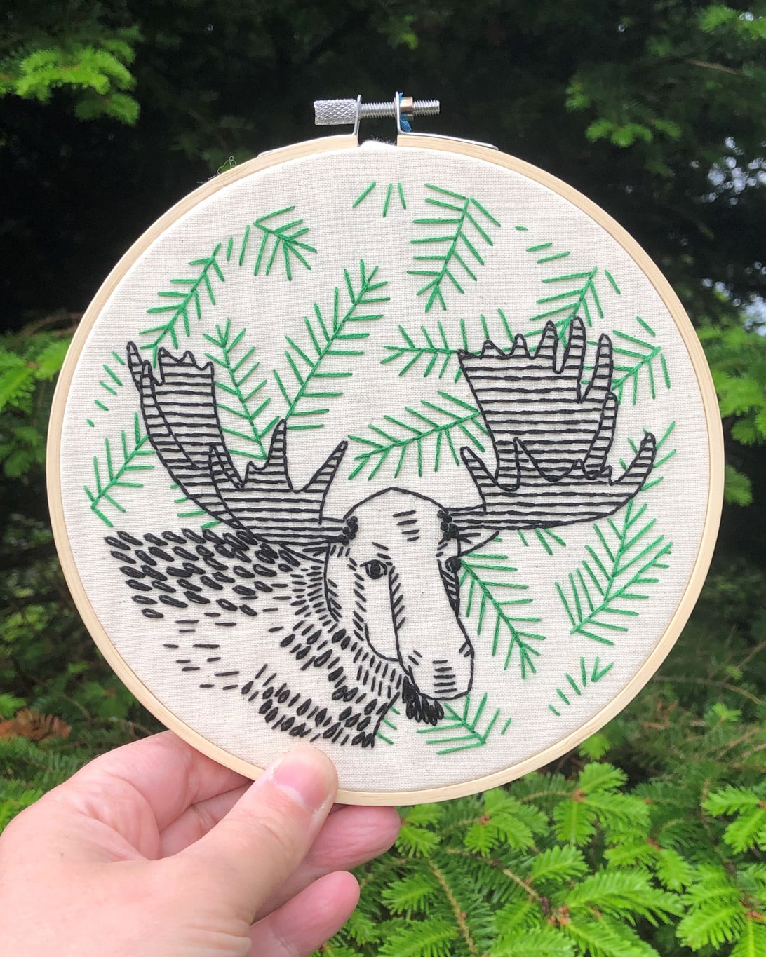 A photo of a green, black and white Moose on the Loose Embroidery Kit