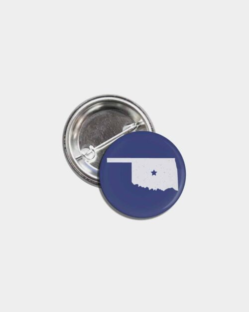 A blue tin pinback button with the state of Oklahoma on it in white.