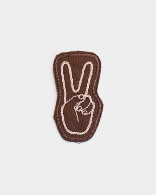 Brown patch with a peace sign stitched in pink on it