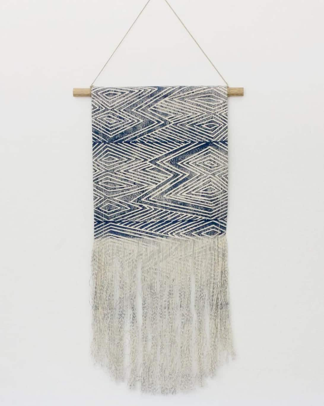 Blue and cream wall hanging on wooden rod