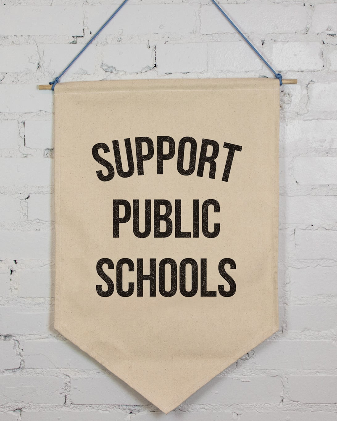 A natural colored canvas banner that says Support Public Schools in black ink