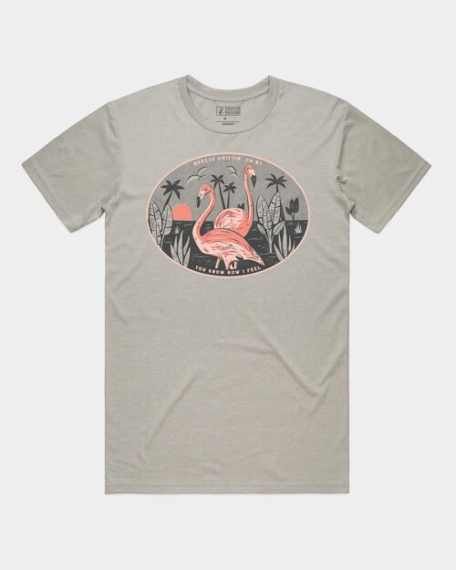 A photo of a grey shirt with Flamingos and bushes on it