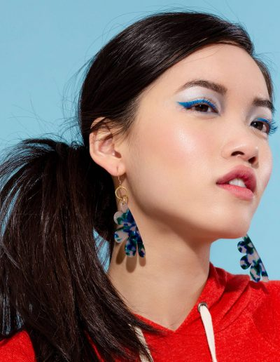 a woman wearing floral shaped earrings with tortoise stone patterns