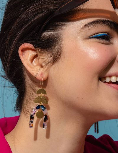 brass earrings with tortoise pendants hanging from them