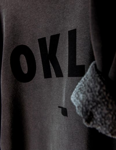 Grey pullover with OKLA printed in black