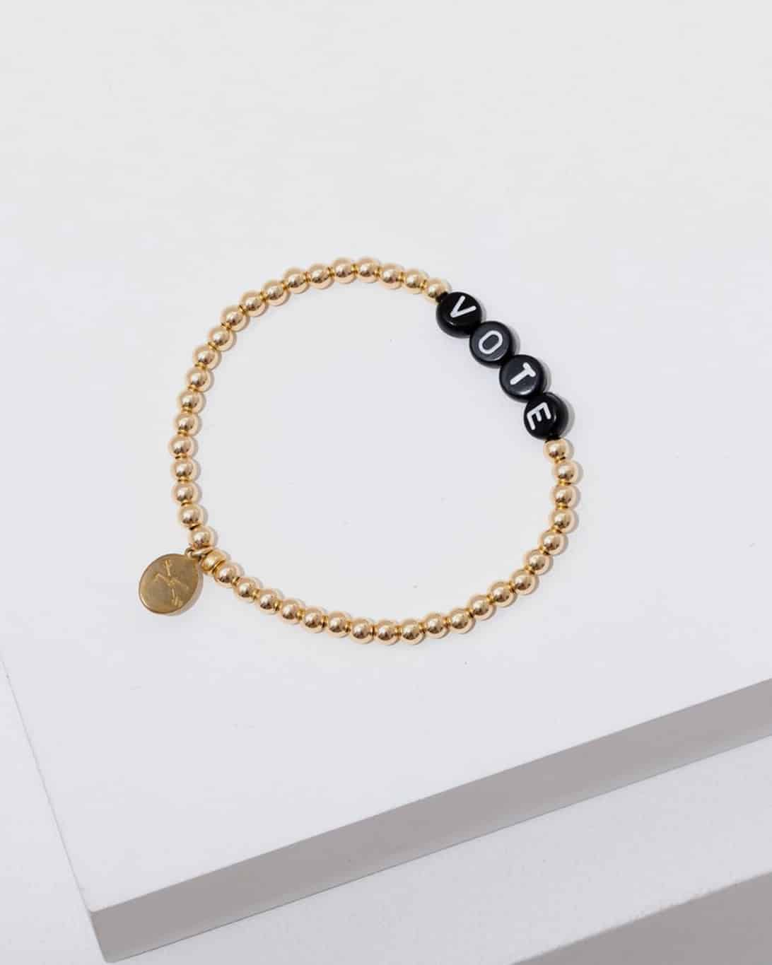 brass necklace that says voite in black letters